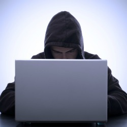 Hooded computer user. Image courtesy of Shutterstock.
